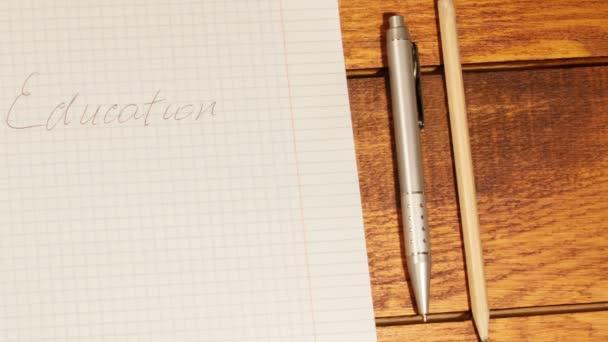 Školní zápisník v kleci s pero a tužka na dřevěný stůl