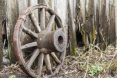 Old classic wooden wheel on old wooden fence background. Copy space