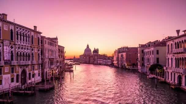Velence, Olaszország - Oktober, 2019: 4k Time Lapse. Napkelte Velencében. Kilátás a Ponte Dell Accademia-tól a Grand Canal-ig. Gondolák és hajóforgalom.