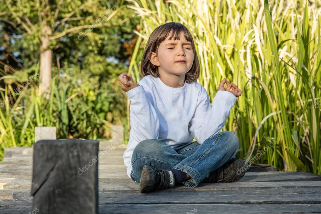 quiet kid doing yoga closing eyes for child serenity