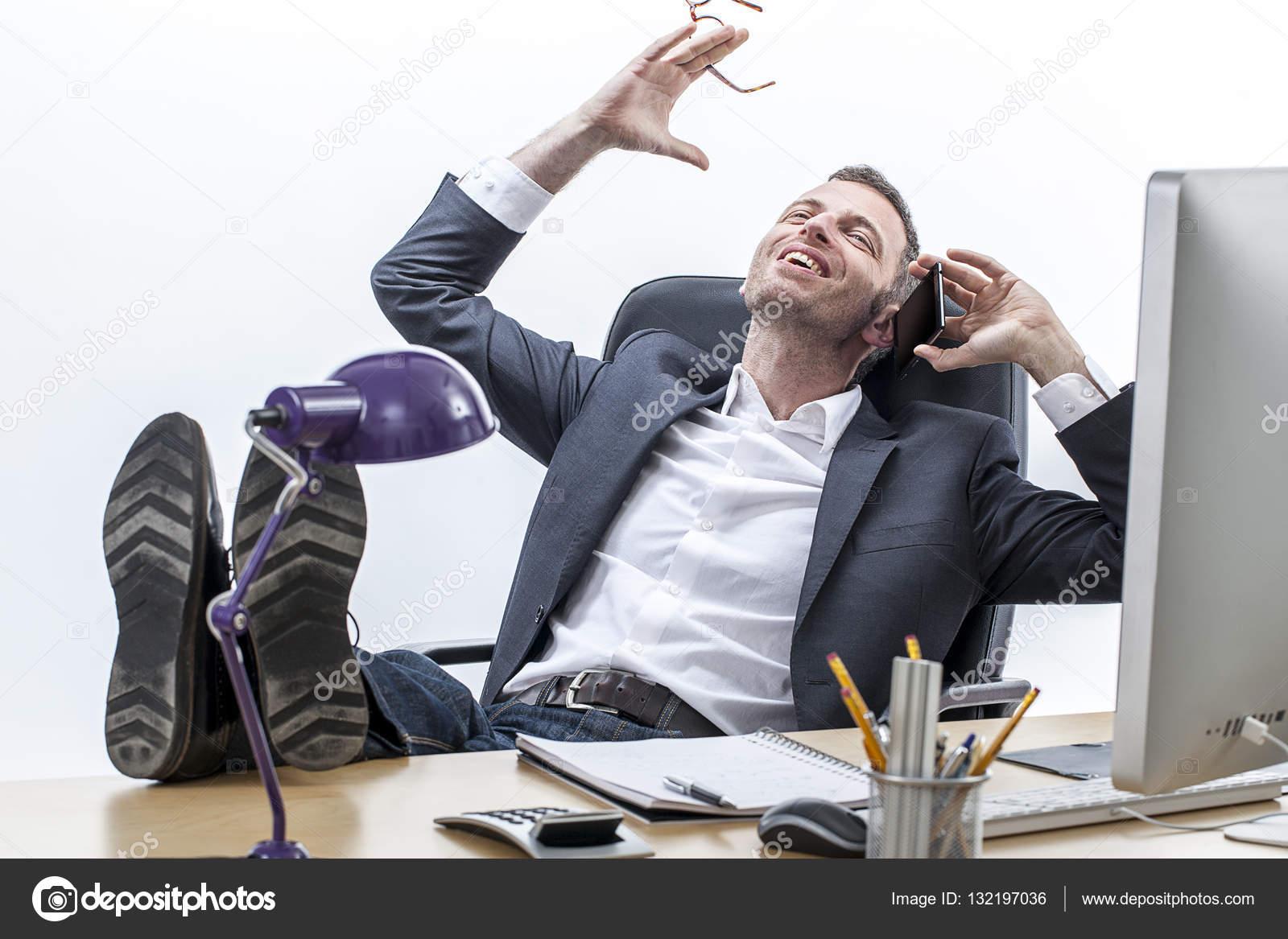 Cool entrepreneur m le avec les pieds sur le bureau en riant sur