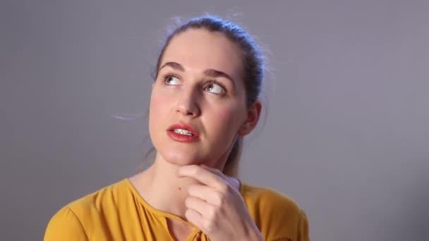 krásná mladá žena drží bradu k nalezení řešení pro dilema