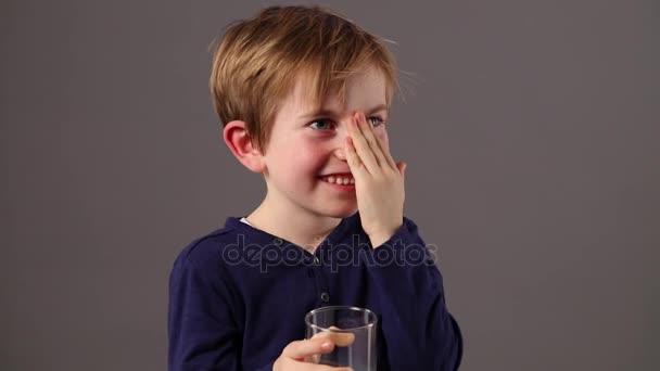 usmívající se dítě drží sklenici mléka dotkla jeho tváře