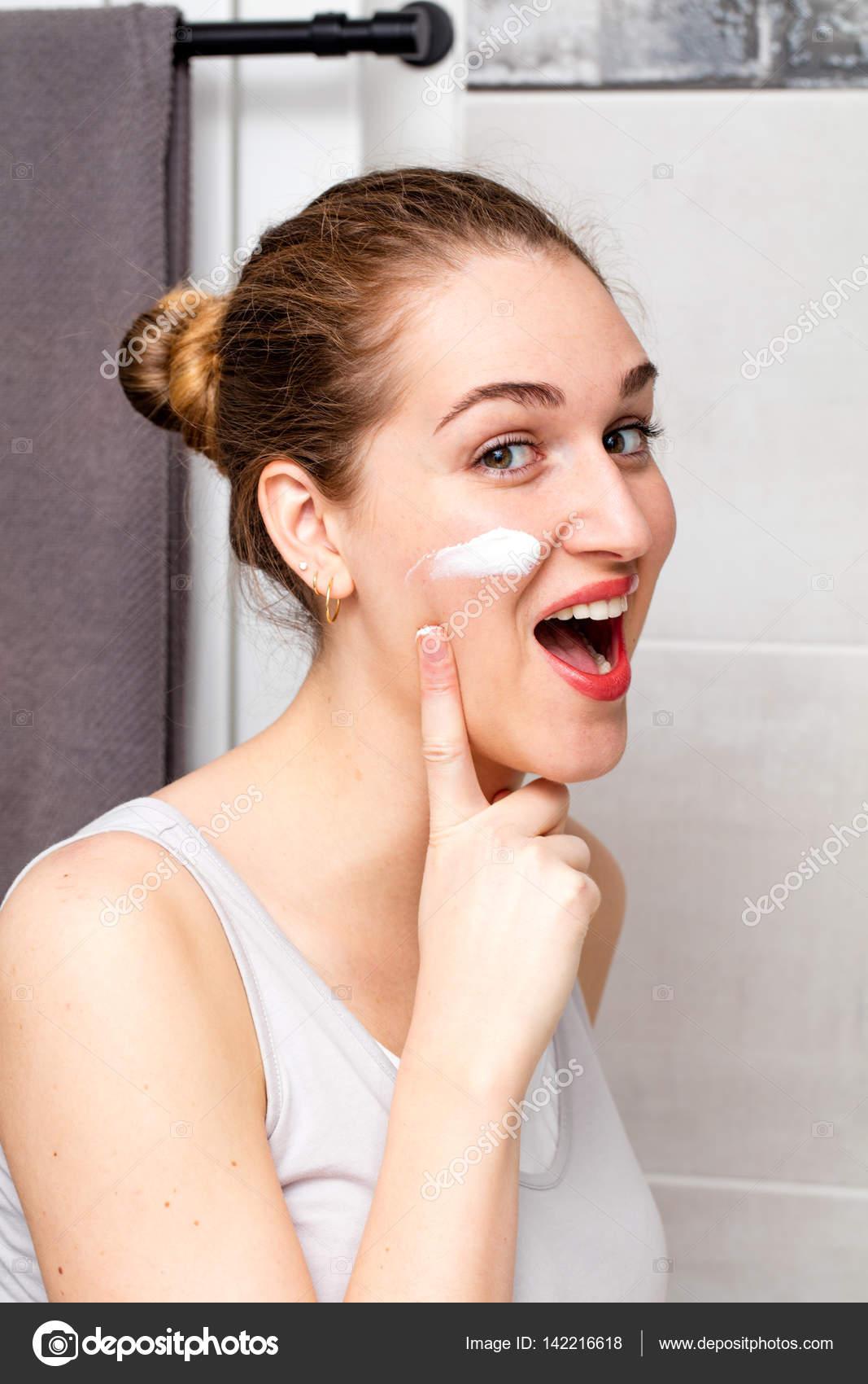 Riendo la crema de cara aplicando disfrutar de hermosa chica en la mejilla — Foto de