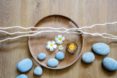 zen flow of pebbles, candle, flowers and twigs over wood