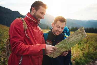 Smiling men reading trail map