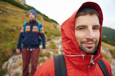 hooded hiker with friend behind him