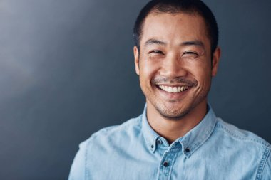 Portrait of a casually dressed confident young Asian designer smiling while standing against a gray wall in an office stock vector