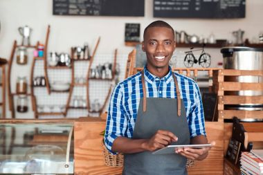 Portrait of a smiling young African entrepreneur in an apron leaning against the counter of his trendy cafe using a digital tablet stock vector