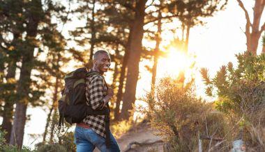 man wearing backpack walking up trail
