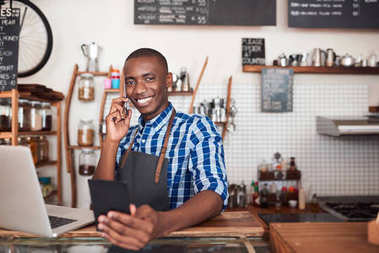 entrepreneur standing at counter of cafe