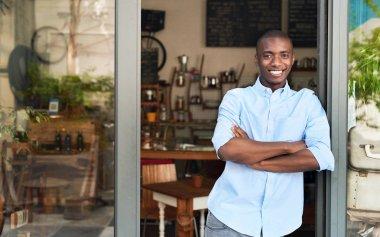 entrepreneur standing at entrance of cafe