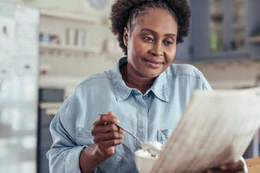 woman reading newspaper and eating breakfast