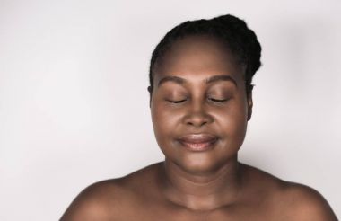 Mature plus size African woman with perfect complexion standing with her eyes closed against a white background