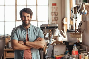 Portrait of smiling young woodworker standing with his arms crossed by workbench full of tools in his carpentry workshop