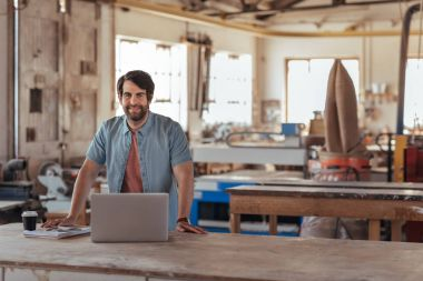 Portrait of smiling young woodworker with beard, leaning over workbench in his large workshop full of carpentry equipment working online with laptop