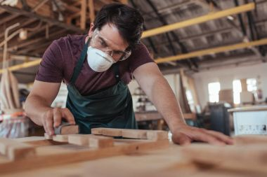 Young craftsman wearing protective mask and glasses skillfully hand sanding pieces of wooden furniture design while working in his large woodworking shop