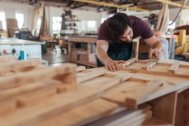 Skilled young carpenter with beard hand sanding pieces of a wooden furniture design while working in his large woodworking shop