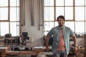 Portrét mladé truhlář usmívající se s jistotou přitom opřený workbench plný nástrojů ve své tesařské dílně