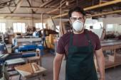 Porträt eines jungen Handwerkers mit Schürze, Schutzmaske und Brille, der allein in seiner großen Tischlerei arbeitet