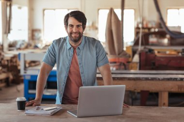 Portrait of a smiling young woodworker with a beard, leaning over a workbench in his large workshop full of carpentry equipment working online with a laptop