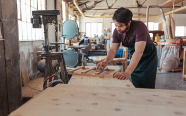 Skilled young carpenter with a beard hand sanding pieces of a wooden furniture design while working in his large woodworking shop
