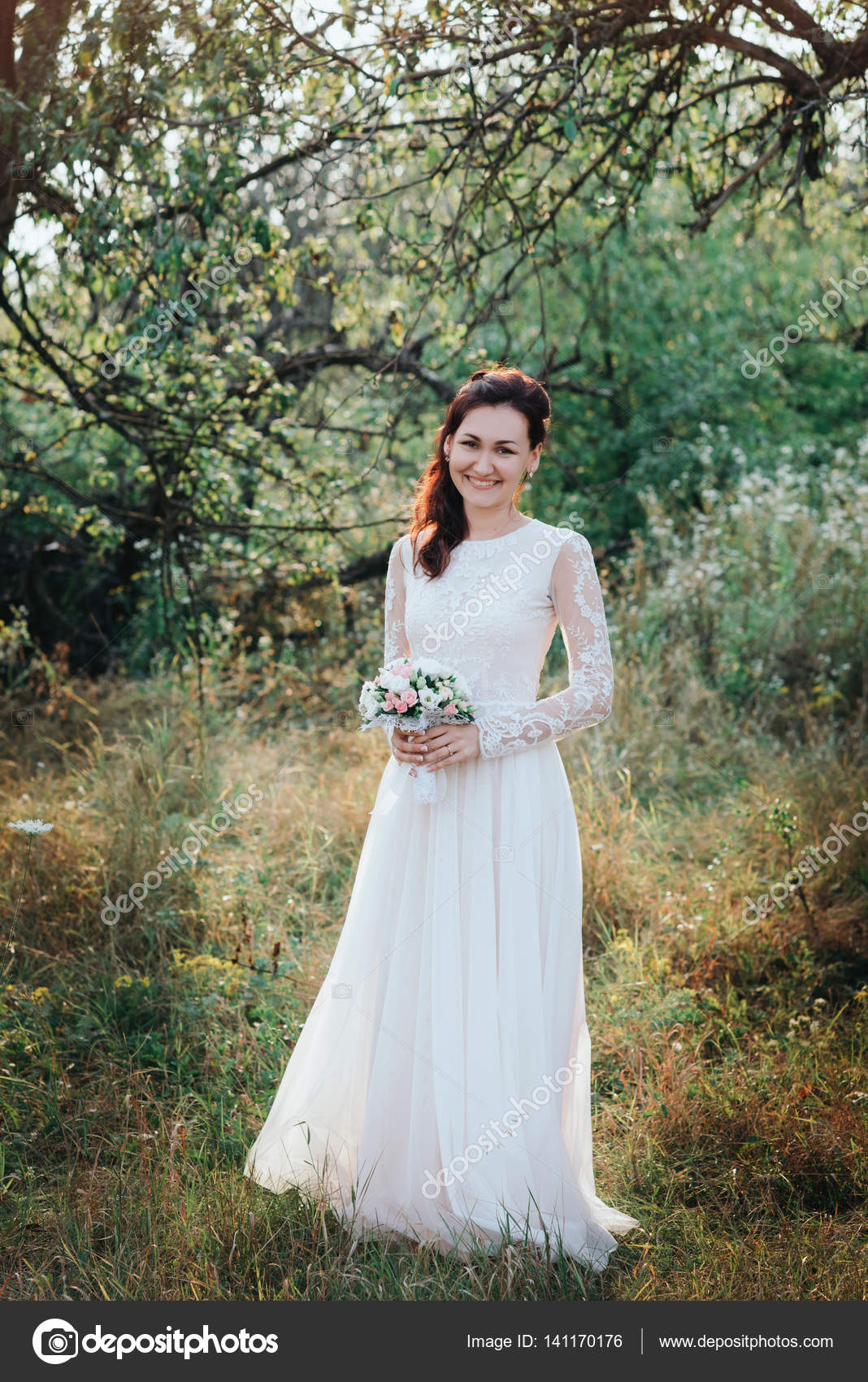 Junge schöne Braut mit Frisur und Make-up posiert in weißen Kleid ...
