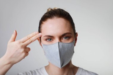 Portrait of young woman in medical face protection mask indoors on white background. Protection of the pandemic virus.