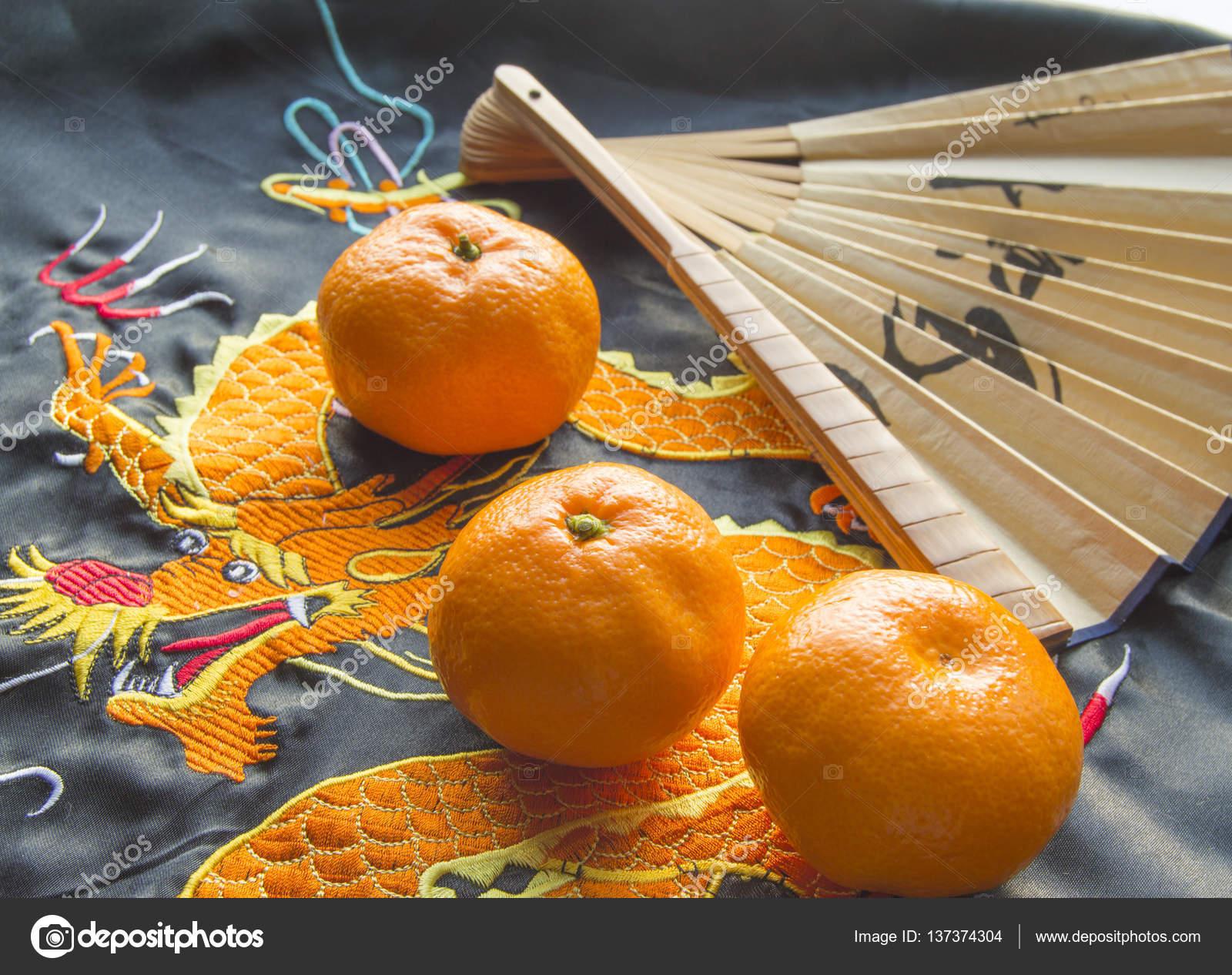 Chinesisches Neujahr, Mandarinen und ein Ventilator auf dem ...