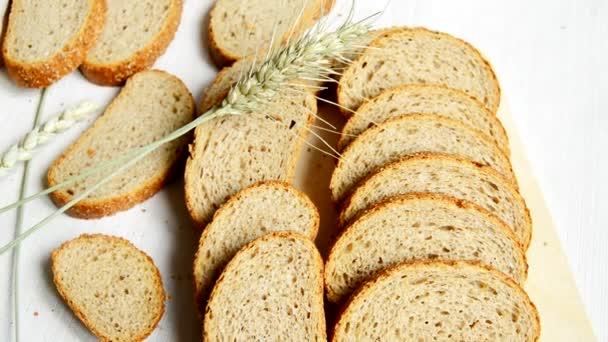 Szeletelt teljes kiőrlésű kenyér az asztalon egy asztalterítő, fülek feküdnek közel, egészséges táplálkozás, egészségügyi nap