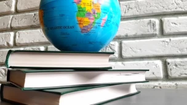 4k video hromada knih a rotující glóbus proti šedé cihlové zdi, koncept vzdělávání, zpět do školy, globalizace, světové problémy