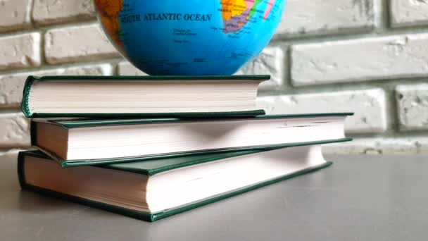 4K video a stack of books and a rotating globe against a gray brick wall, the concept of education, back to school, globalization, world problems
