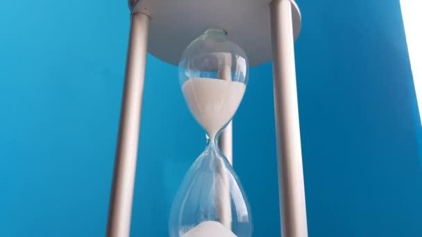 Elegáns homokóra kék háttérrel. Koncepció-üzleti idő pénz, oktatás, idő fogy, időgazdálkodás, időforrás, teljes munkaidő, határidő.