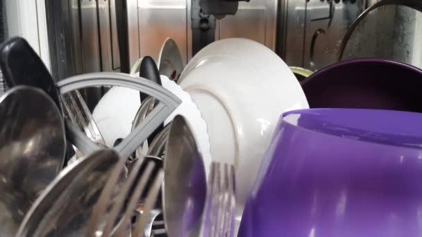 Pomocí moderní myčky nádobí v domácnosti, ruce hospodyně vzít čisté nádobí z myčky nádobí, zblízka. Moderní domácí spotřebiče doma. Video 4K