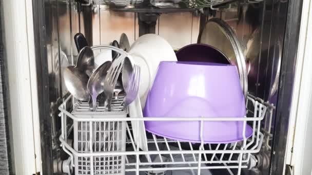 Pomocí moderní myčky nádobí v domácnosti, ruce hospodyňky vzít čisté nádobí z myčky nádobí, zblízka. Moderní domácí spotřebiče doma. Video 4K