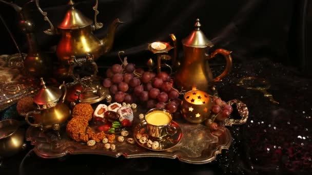 Ženské ruce s orientální šperky dělat čaj do šálku. Tradiční marocké sladkosti. Hrnek mléka šafrán Masala čaj