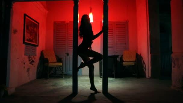 Sexy žena silueta tančí v hotelu. Pole tanečnice ženské striptérka v noci bordel. Smyslné červené světlo, noir styl