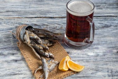 Small, salted fish with a glass of dark beer. Near the slices of lemon. On a light, wooden background.