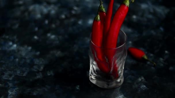 leuchtend rote Chilischoten in einem transparenten Glas auf dunkelblauem Hintergrund. Farbtrend
