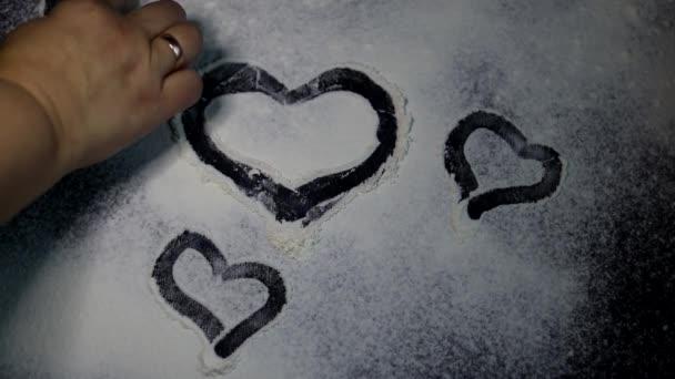 Mehl wird auf den Tisch gestreut. zeichnen sie mit einem Finger ein Herz darauf. Valentinstag. dunkel marmorierter Hintergrund. Weißmehl.