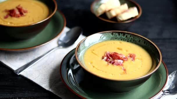 Čočková polévka na dřevěném pozadí. Servírujeme s krájenou slaninou a bylinkami. Nedaleko jsou kousky ciabaty. Syrové krupice v pozadí.