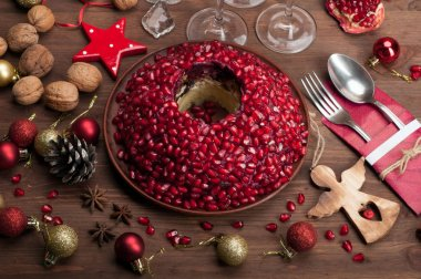 Christmas and New Year's menu: salad 'Garnet Bracelet'  (which contains potatoes, fried onions, fried chicken, boiled beets and pomegranate grain) on brown wooden background. Beside cutlery, Christmas decorations, spices , cones, tinsel etc.