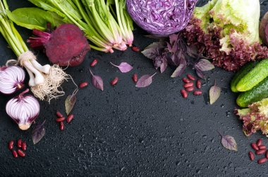 Vegetable background (wallpaper). Bright juicy purple and green vegetables and herbs on a black background with water drops. Red cabbage, purple onion, spinach, lettuce, cucumbers and basil. Space for text. Vegetarian, vegan concept