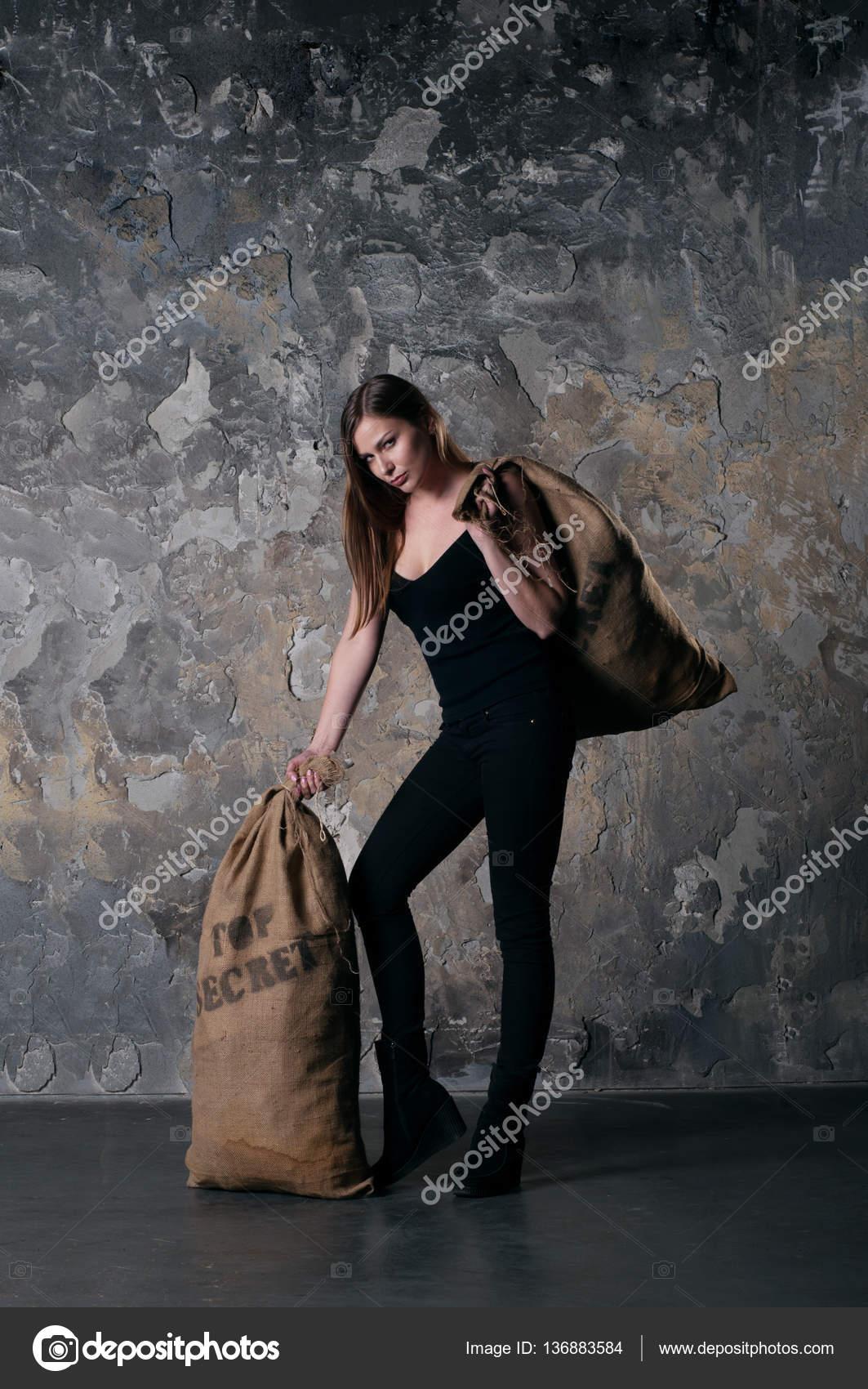 00f3cf7eb8c686 Schöne junge Frau (Mädchen) mit langen braunen Haaren in ein schwarzes  t-Shirt und schwarze Jeans halten einen Beutel mit der Aufschrift 'Streng  geheim' ...