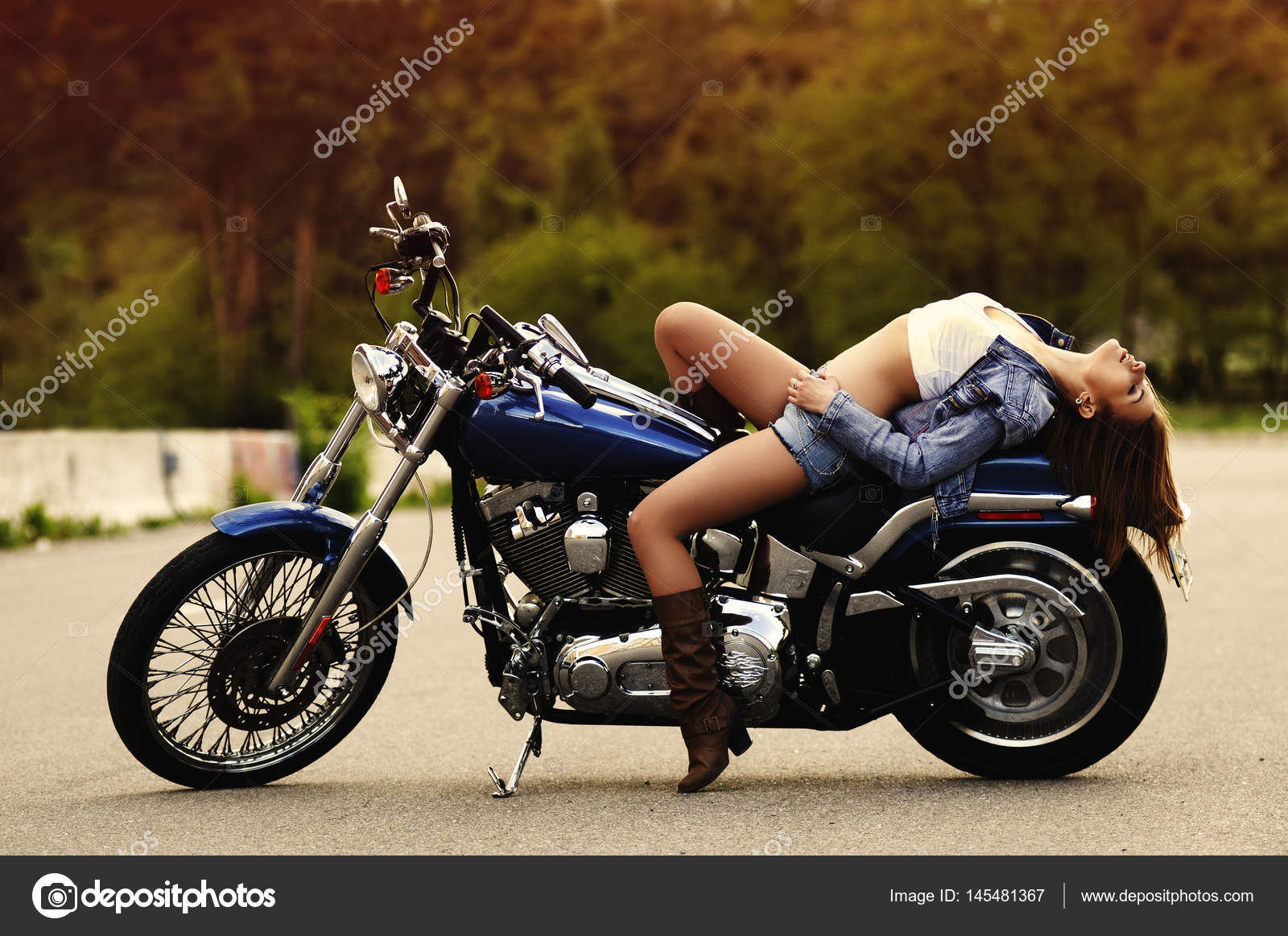 a motorcycle shooting  A beautiful slender young woman (girl) lies on a motorcycle against ...