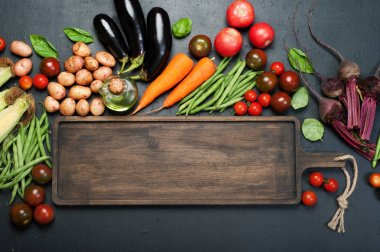 Vegetable background. A long brown wooden cutting board (tray), next to which lie fresh organic vegetables such as carrots, beets, asparagus beans, tomatoes, eggplant, on a dark surface. Place for text on the cutting board