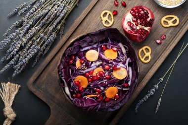 Dietary low-calorie salad of red cabbage, carrots, pomegranate seeds and olive oil in a wooden plate bowl. Nearly half a pomegranate and lavender flowers. Vegetarian, vegan concept stock vector