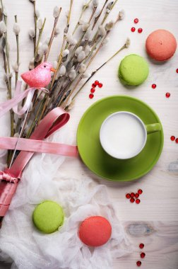 Coffee with whipped milk in a green cup on a white background. Near the willow branches with a pink bird (decoration) and sweets (macaroons)