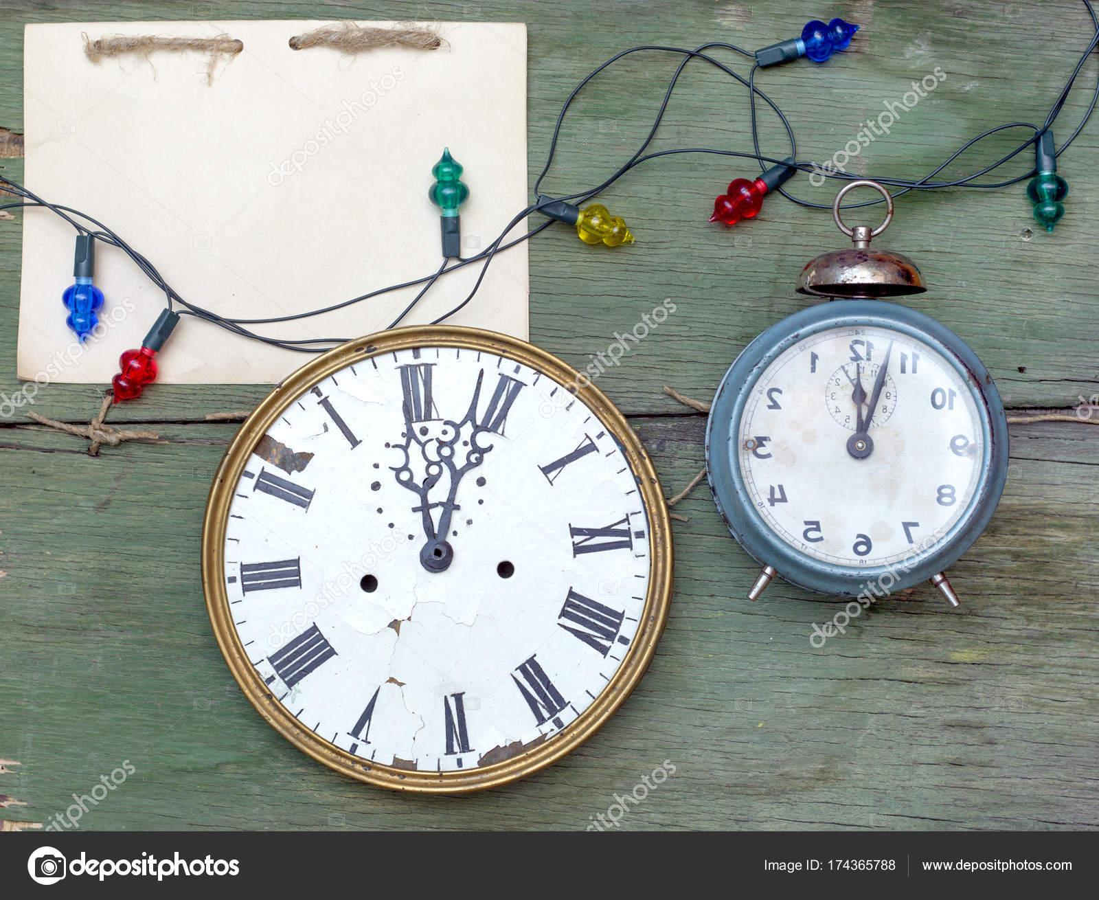 64c4f6c98d1 Ano novo antigo relógios na verde descascando fundo de madeira. Embalagem  artesanal em branco o bloco de notas. Maquete de férias — Foto de  rtyt01.mail.ru