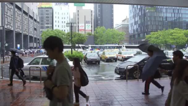 Fukuoka, Japan - 13 July 2019 - Taxi cabs wait for customers at the entrance of Hakata train station in Fukuoka, Japan on rainy day of July 13, 2019